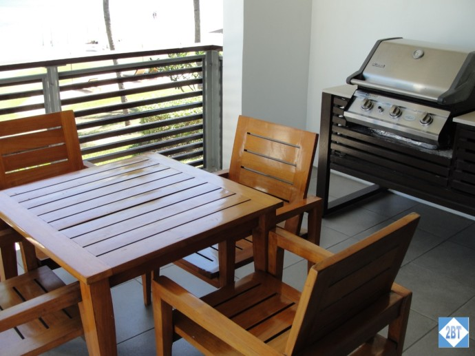 On the balcony: tables, chairs and a grill