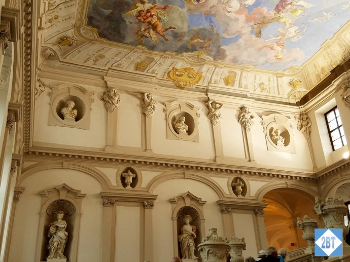 Sculptures surrounding the staircase underneath the frescoed ceiling