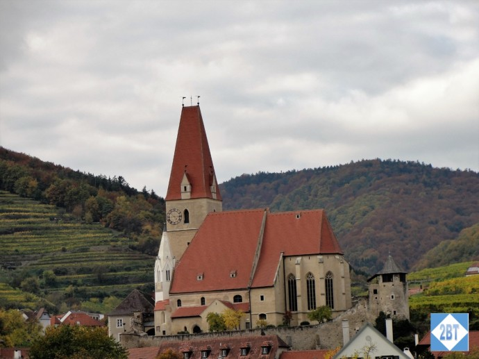 A church in the Wachau Valley with vineyards in the background