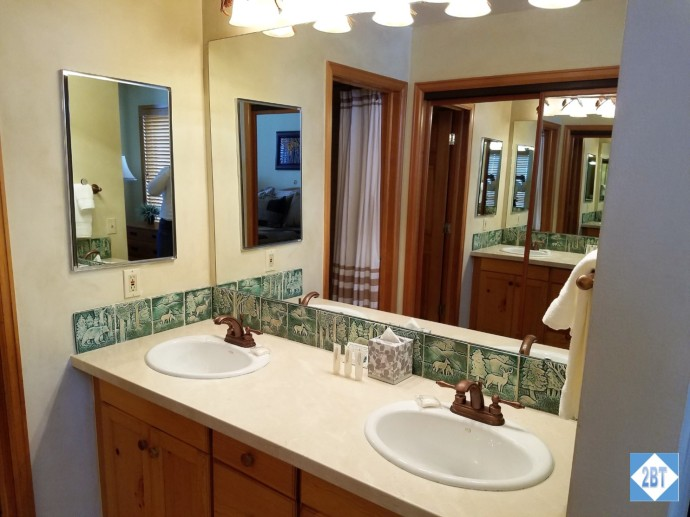 Double sinks in the second bath with the closet reflected in the mirror