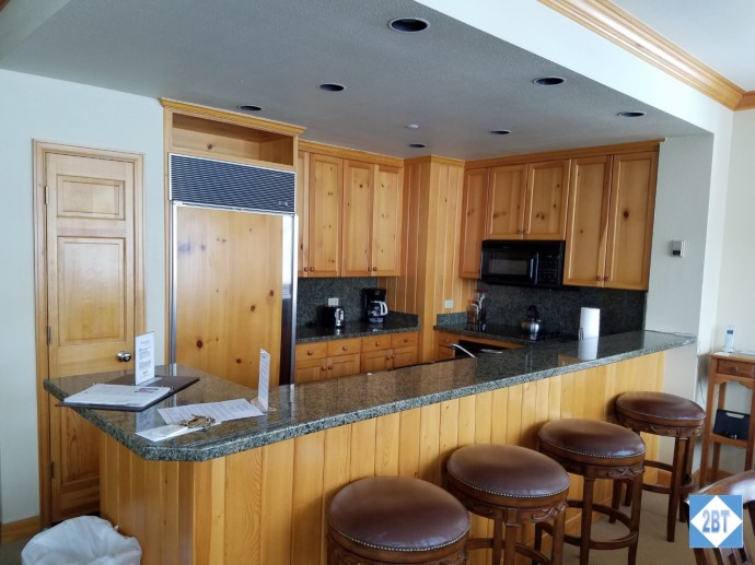 The kitchen includes a pantry and a number of bar stools
